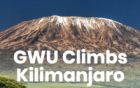 photo: text GWU Climbs Kilimanjaro in the foreground, Mount Kilimanjaro sits snowcapped in the background
