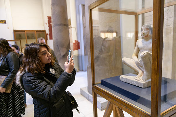 Student taking a photo in the Egyptian Museum