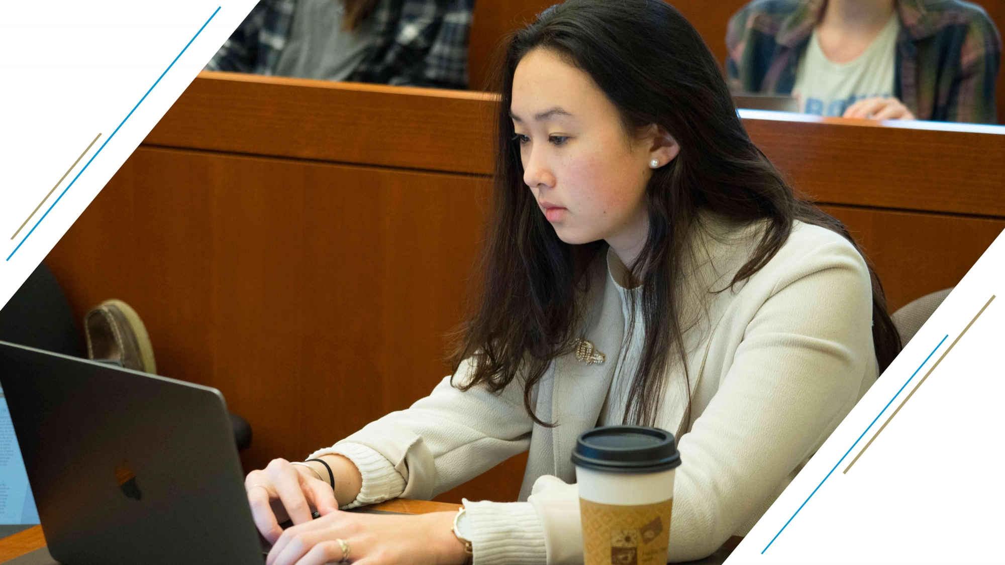 photo: student taking notes on a Mac laptop while in class