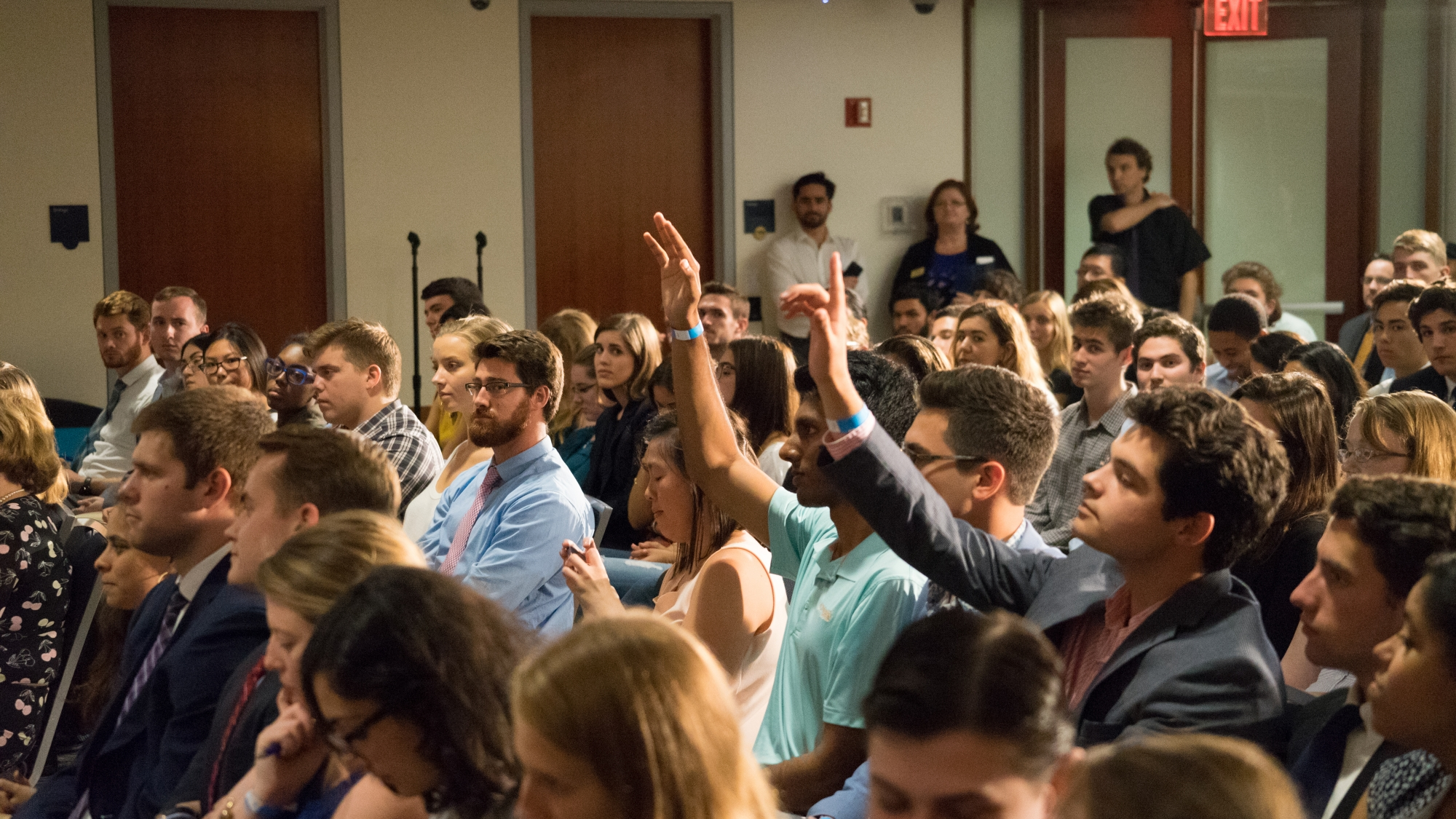 Photo: Audience members raise hands to ask a question to former Director of National of Intelligence James Clapper