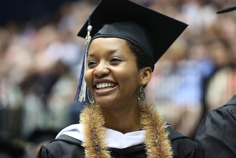 Student smiles in graduation regalia in the Smith Center