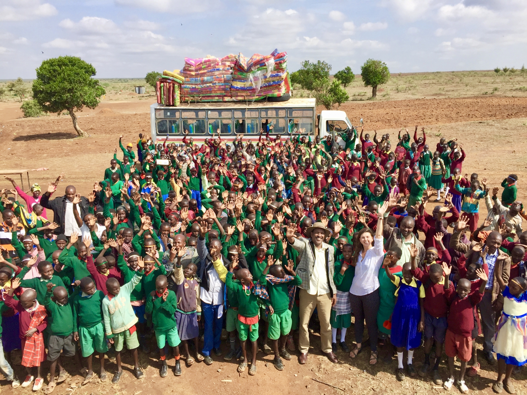 photo: Taking place in Kenya, GW student Francesca Diggs stands in the middle of a group of over 50 children in front of a school bus. The children, who are waving and smiling with excitement, are wearing vibrant green and red traditional uniforms. Behind them is the serene, vast landscape of Kenya