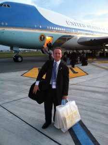 photo: David Solomon stands outside of Air Force One, he carries a suitcase and appears to be about to board the plane.