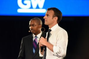 image: Dean Brigety poses with President Emmanuel Macron, Macron holds a microphone and both figures look towards the audience