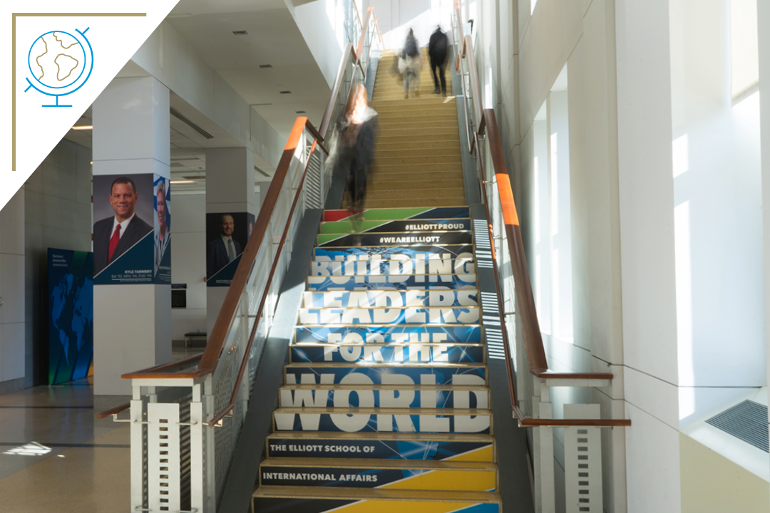 photo: Elliott School main staircase with a handful of students walking up and down it. The staircase has the text #ElliottProud, #WeAreElliott, and Building Leaders for the World printed on it