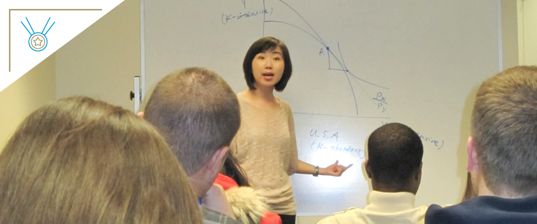 photo: Professor Maggie Chen stands in front of a classroom filled with students mid-lecture. Behind her is a whiteboard filled with graphs, notes, and other writing. In the corner is a drawing of a medal with a star on it, indicating that she has won an award.