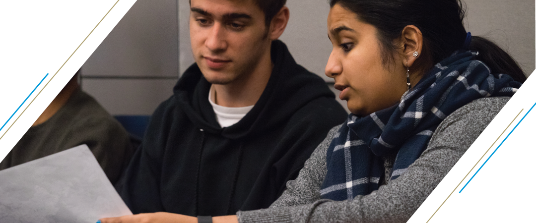 photo: two students sitting in lecture lean in close together as they confer over a piece of paper