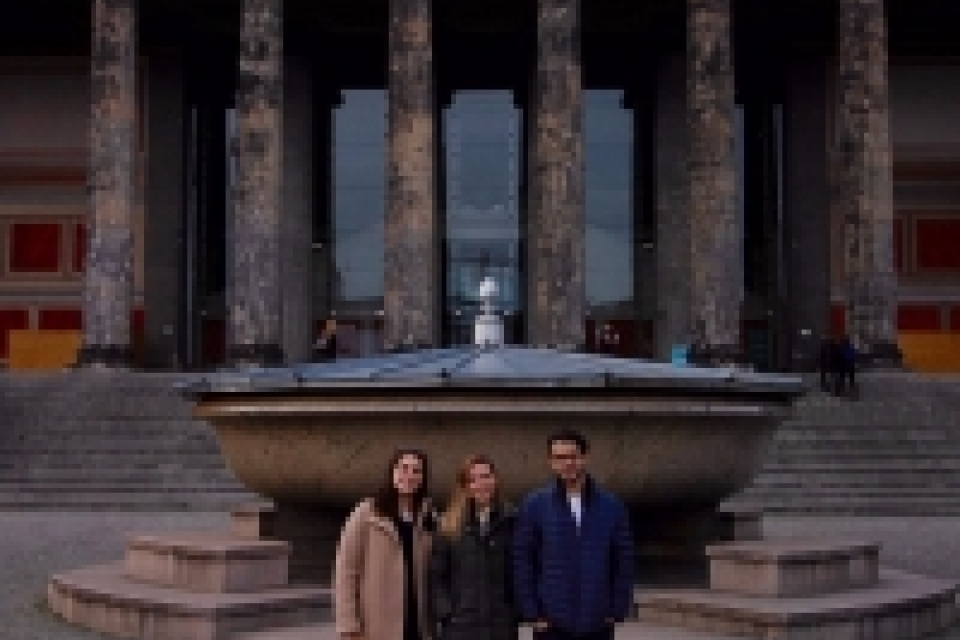 photo: three students stand in front of a fountain. Behind the fountain is a building with columns