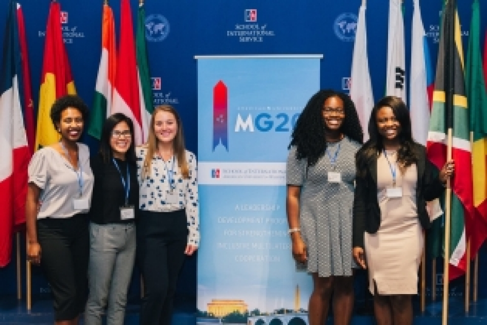 photo: five students stand in front of the Model G20 Summit Program logo