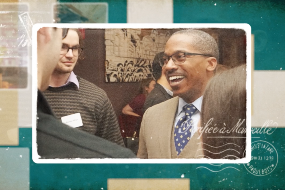 photo: a rectangular frame around a photo of Dean Brigety smiling at three students who stand next to him.