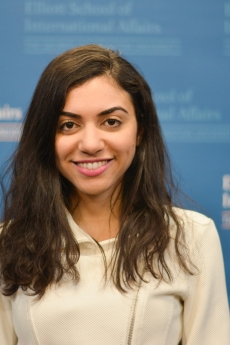 Photo: Headshot of Farah Farid in front of a step and repeat banner of the Elliott School of International Affairs logo