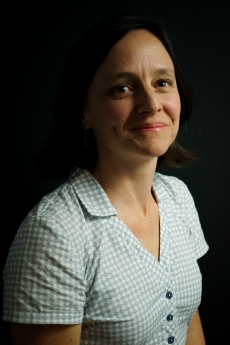 Photo: Headshot of Amy Stearns with black background