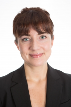 Headshot: Shana Marshall smiling in front of a white background
